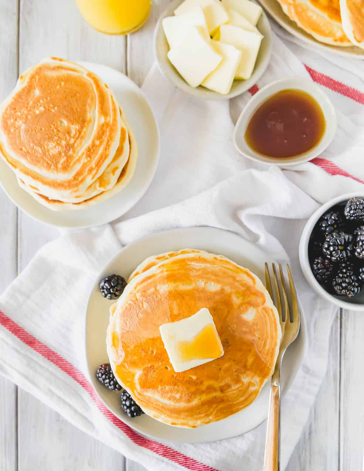 Overhead view of pancakes, blackberries, and syrup.