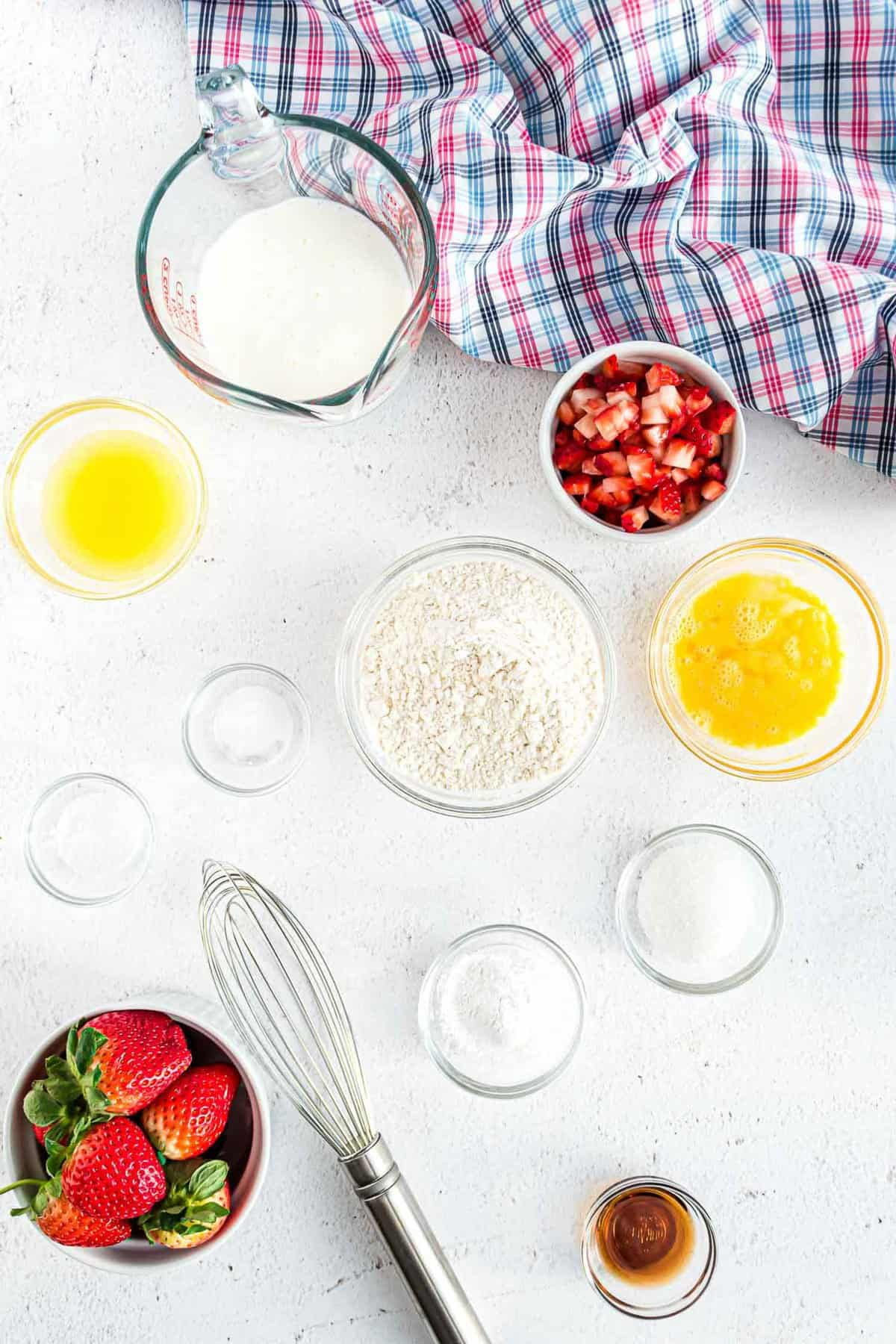 Overhead view of ingredients in bowls: strawberries, flour, butter, vanilla, and more.