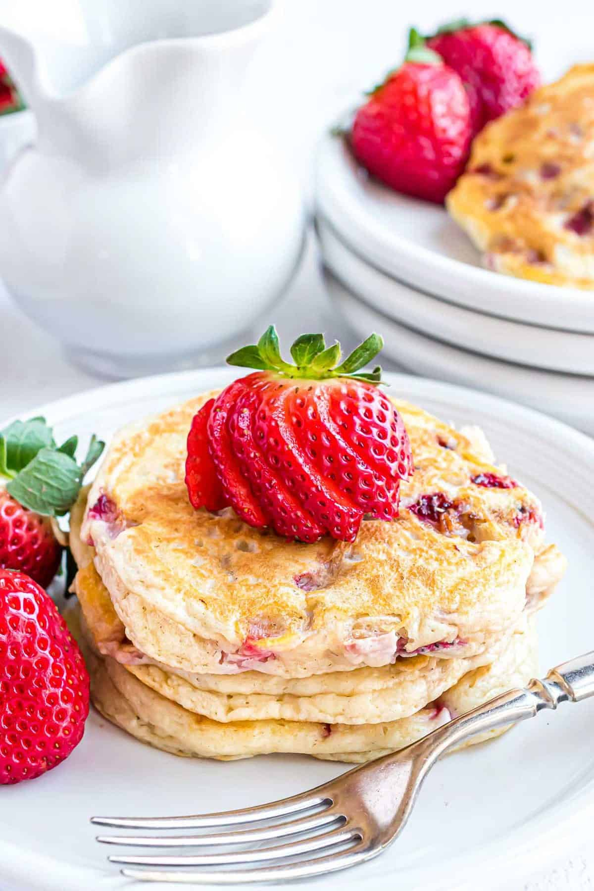 Pancakes topped with a sliced strawberry.