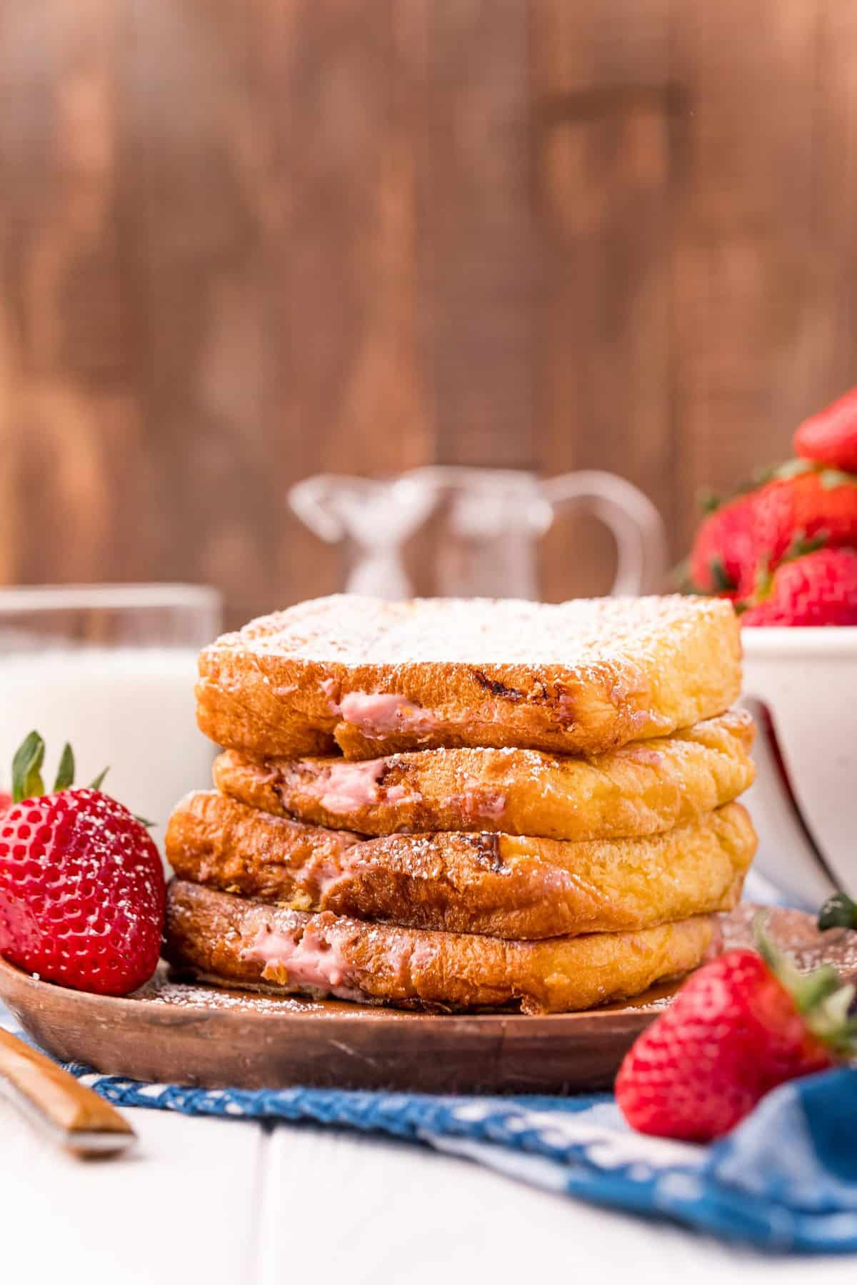 Stack of french toast surrounded by fresh strawberries.