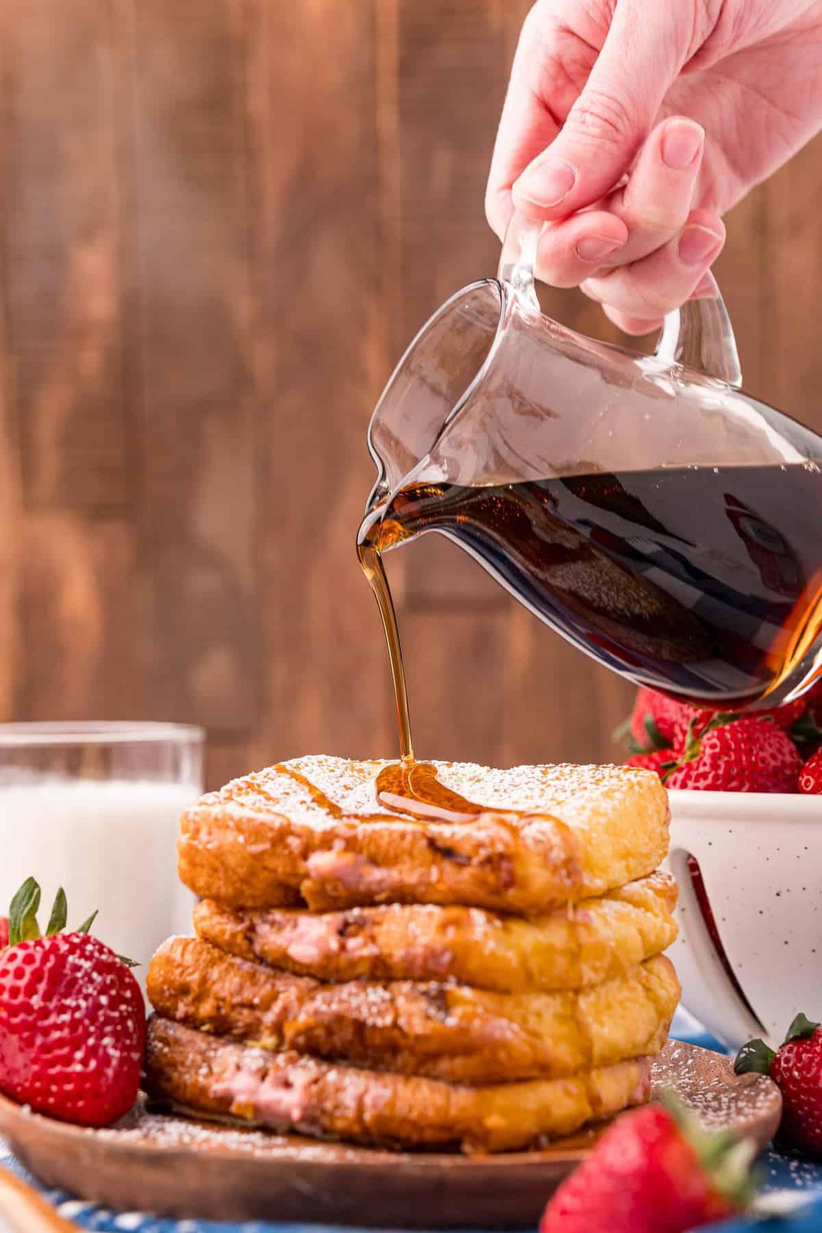 Maple syrup being poured on a stack of french toast.