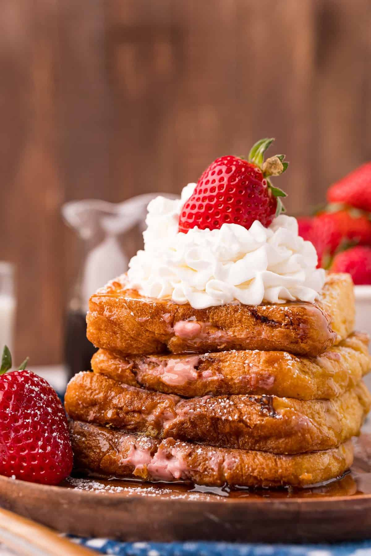 Stack of stuffed french toast with whipped cream and strawberries.
