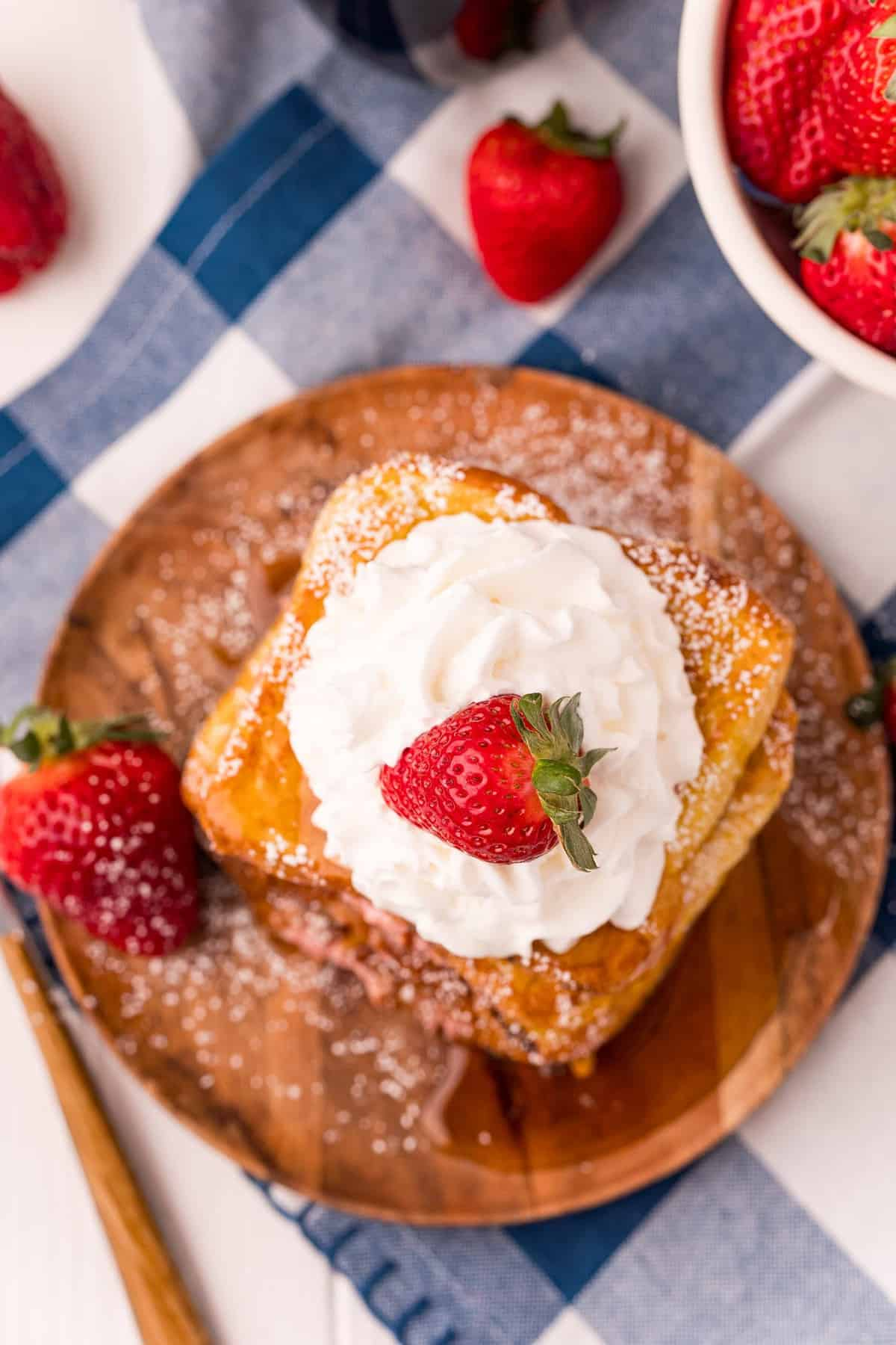 Overhead view of strawberry cream cheese french toast with whipped cream.