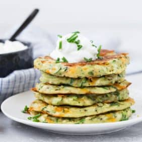 Stack of zucchini fritters on a white plate, topped with sour cream and fresh chives.