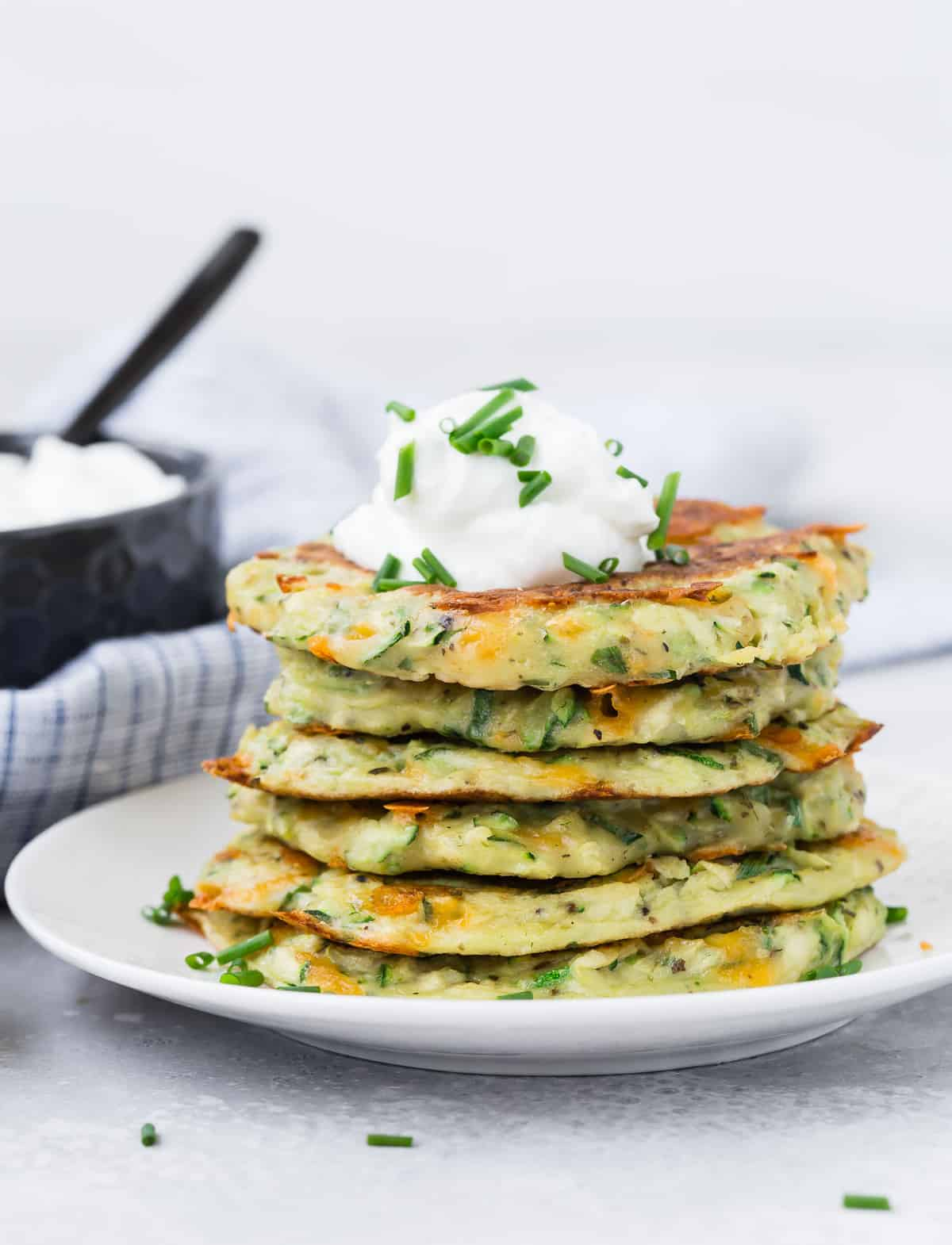A stack of zucchini pancakes on a white plate, topped with sour cream and chives.