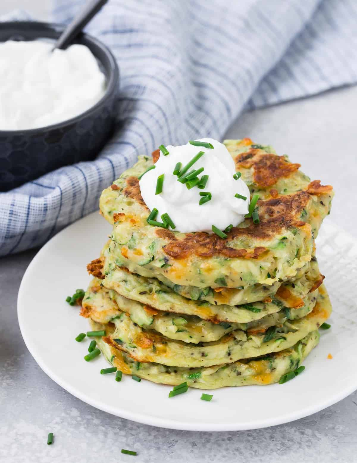 Fritters made with zucchini in a stack on a white plate.