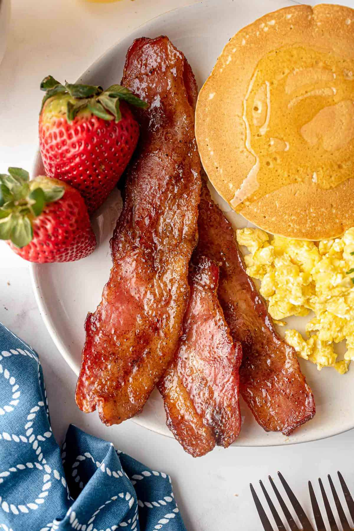 Bacon on a plate with pancakes, eggs, and strawberries.