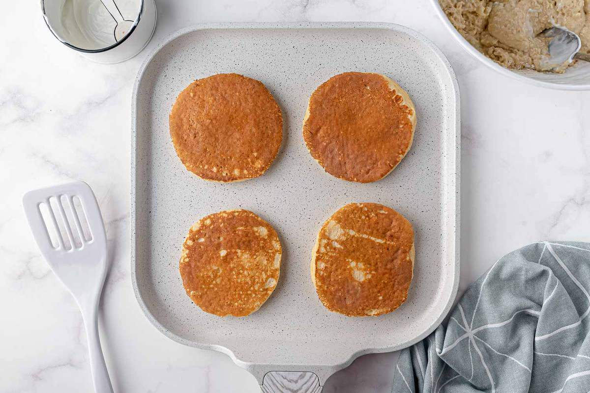Cooked pancakes on a white griddle.