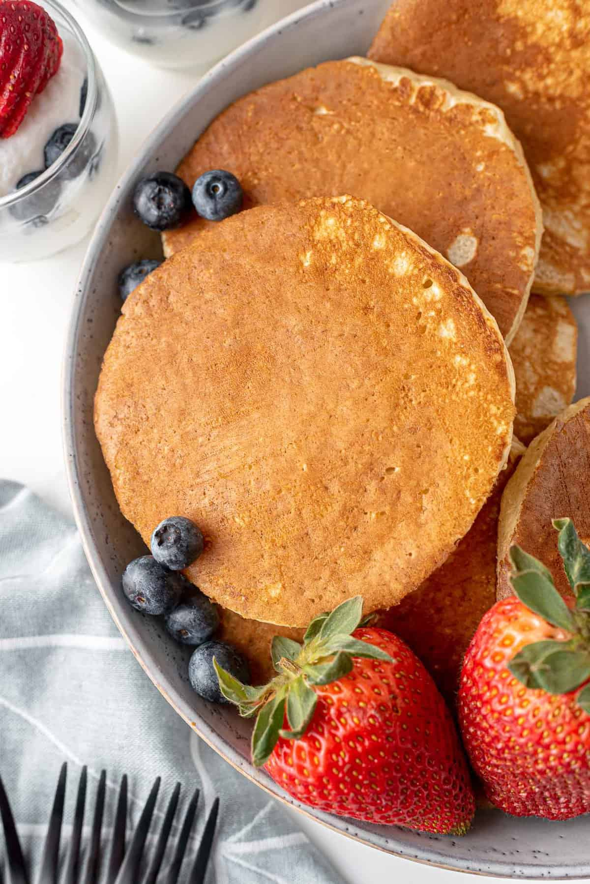 Overhead view of pancakes on a platter with fresh fruit.