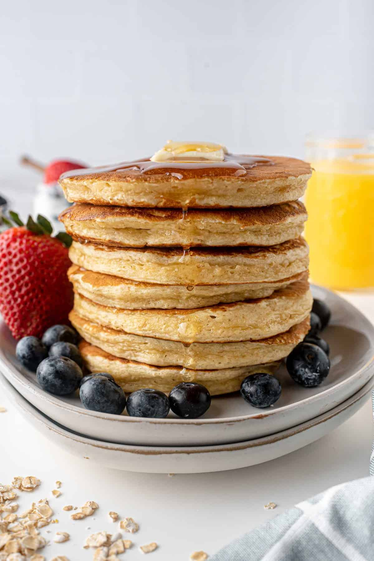 Tall stack of pancakes, surrounded by fresh fruit, dripping with maple syrup.