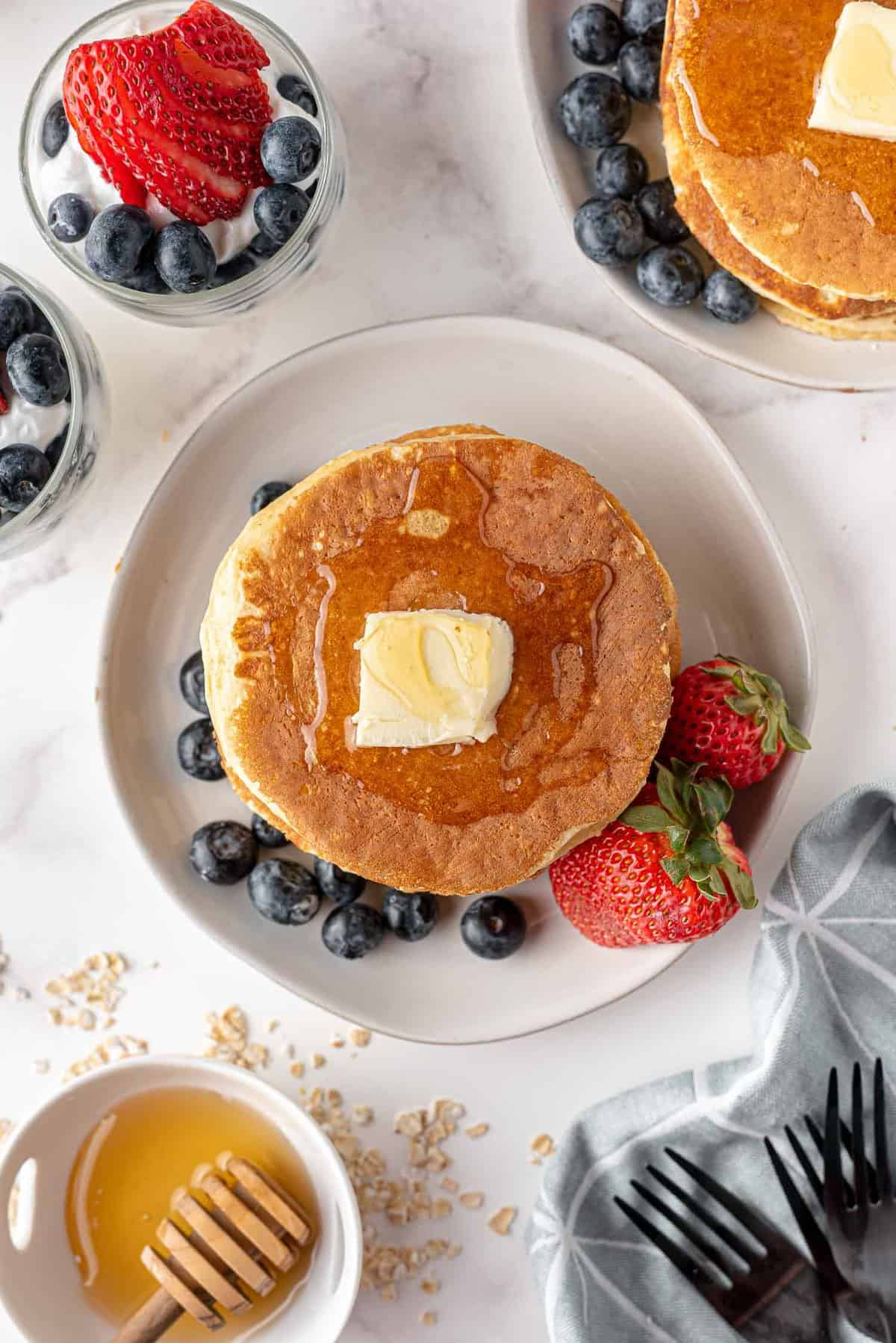 Overhead view of pancakes topped with butter and syrup.