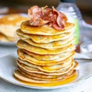 Tall stack of pancakes topped with bacon.
