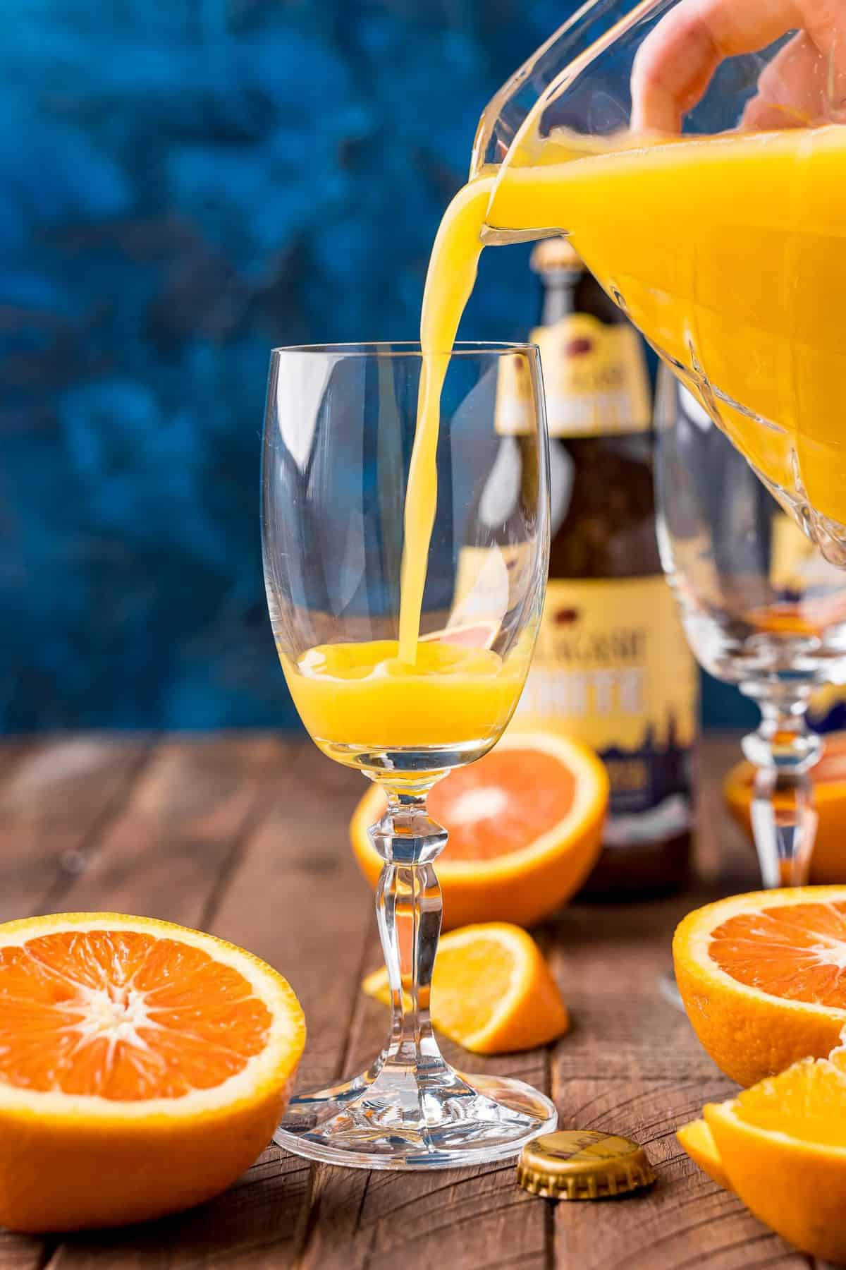Orange juice being poured into a champagne flute.