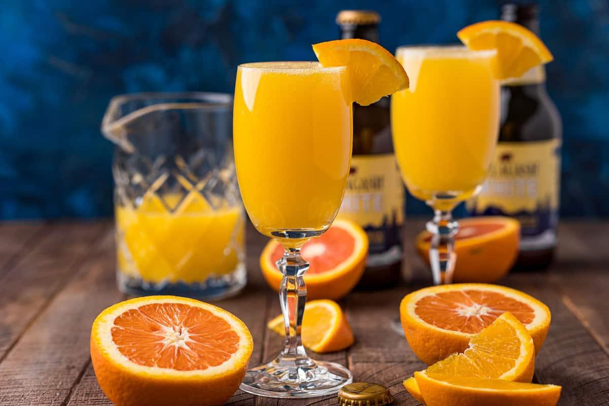 Two orange cocktails in stemmed glasses against a dark blue background.