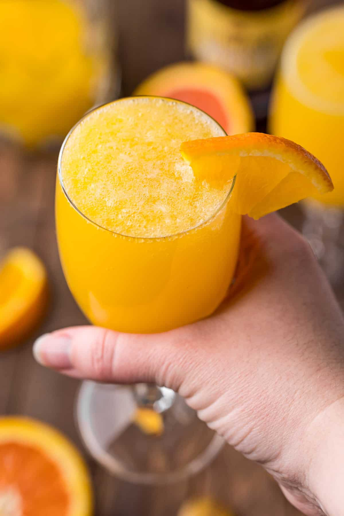 Beermosa, garnished with an orange slice, in a hand.