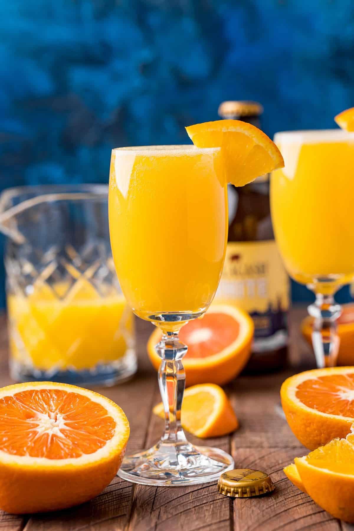 Orange juice based cocktail in a stemmed glass against a dark blue background.