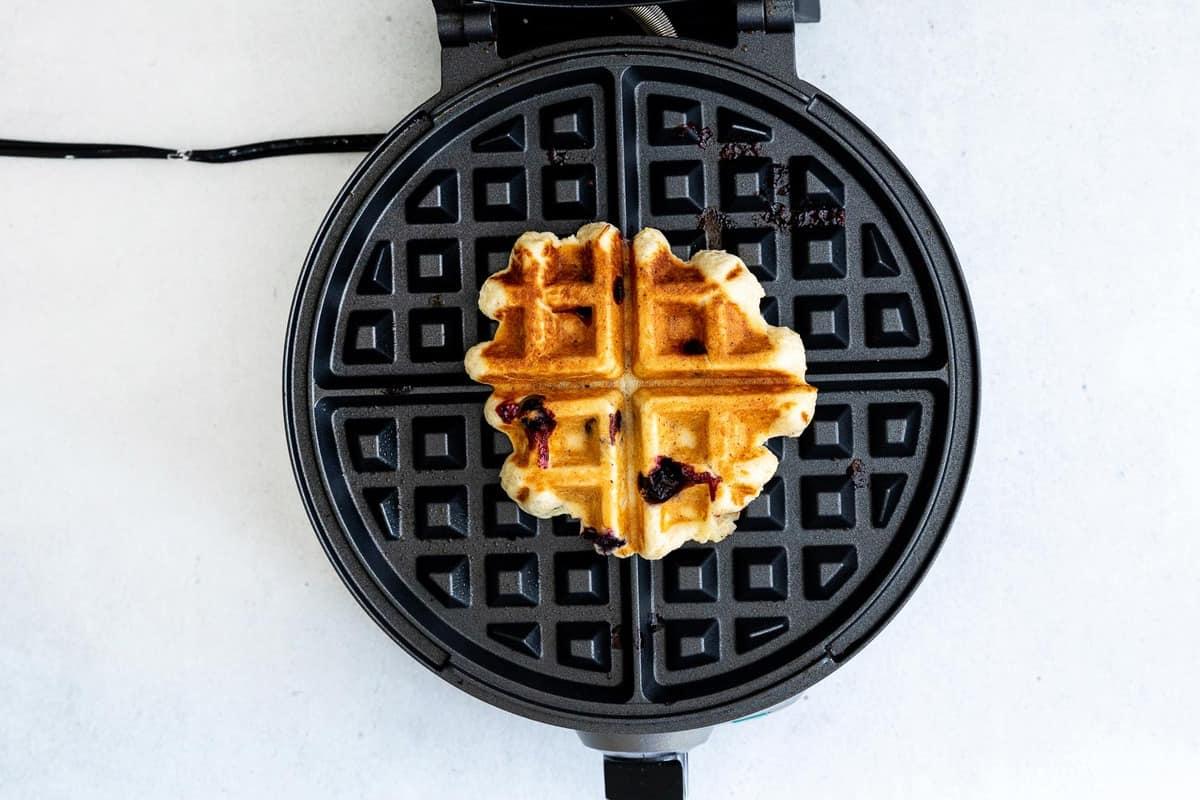 Waffle in black round waffle maker.
