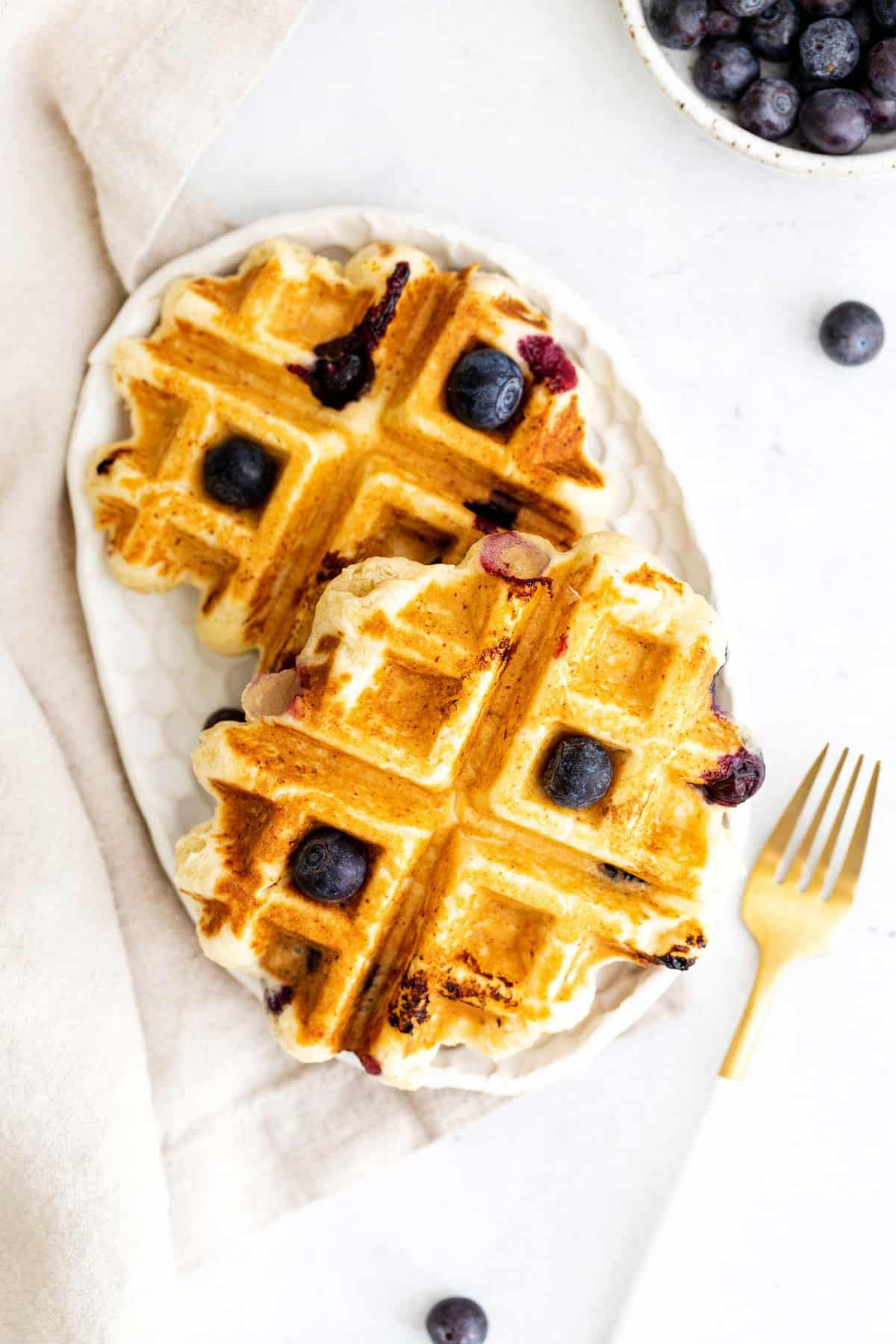 Waffles on a small oval plate, sprinkled with blueberries.
