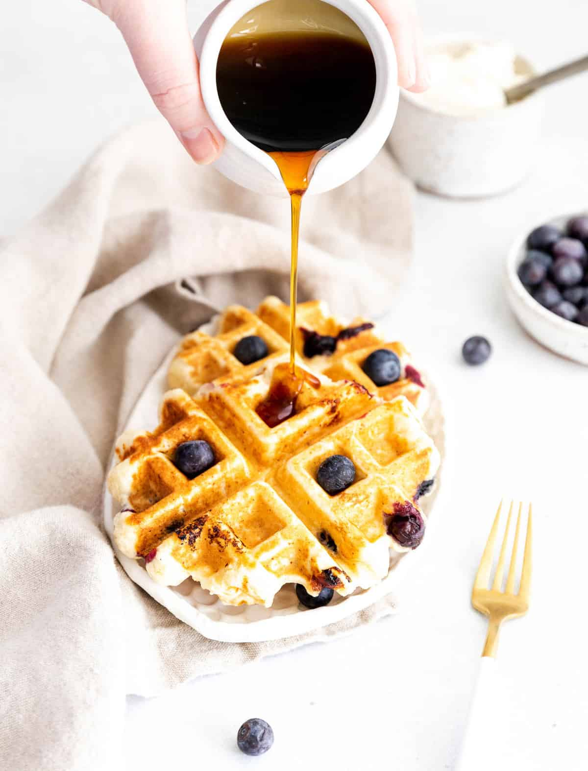 Syrup being poured on two small waffles topped with blueberries.