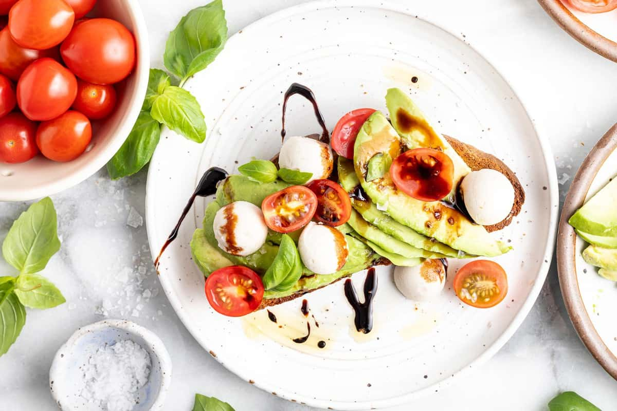 Toast topped with avocado, tomatoes, mozzarella, basil, and balsamic.