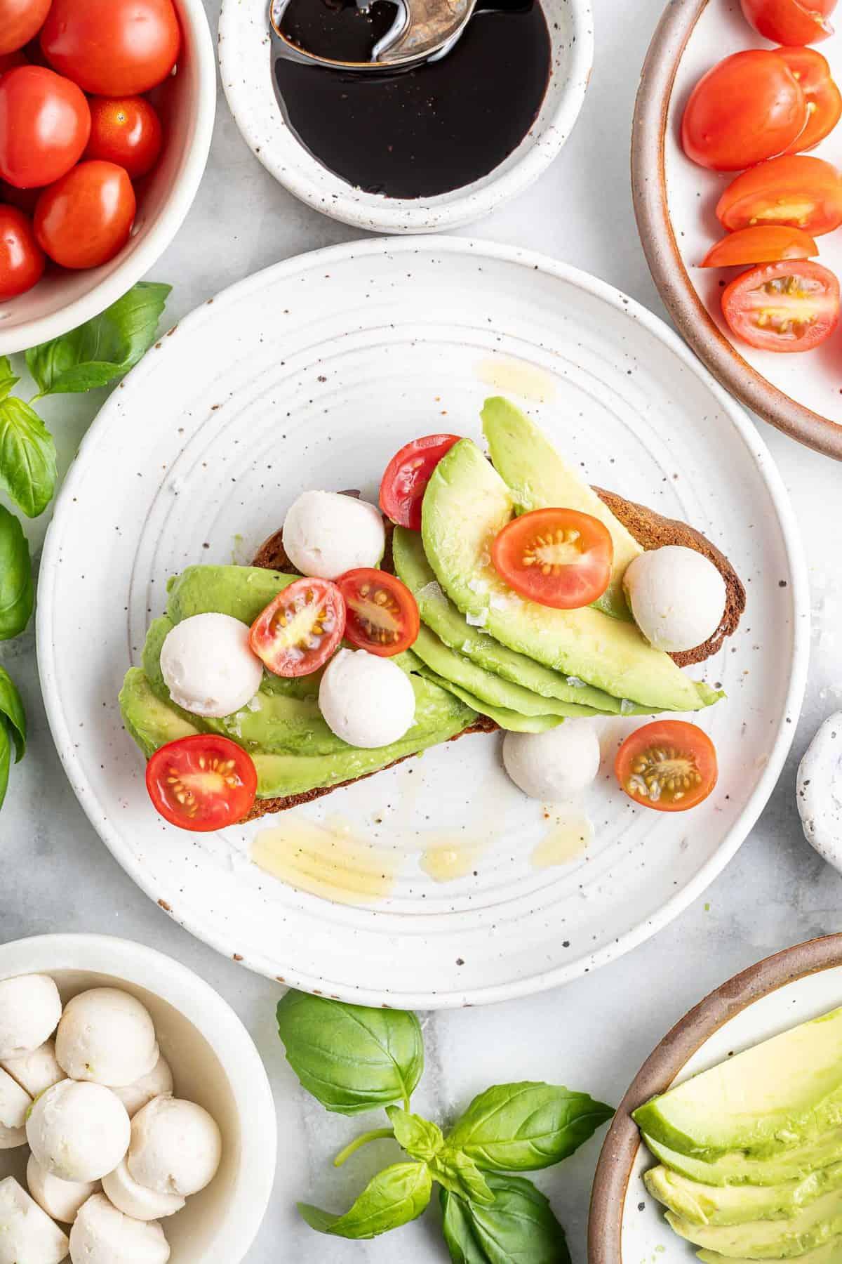 Avocado toast topped with fresh mozzarella and fresh tomatoes.