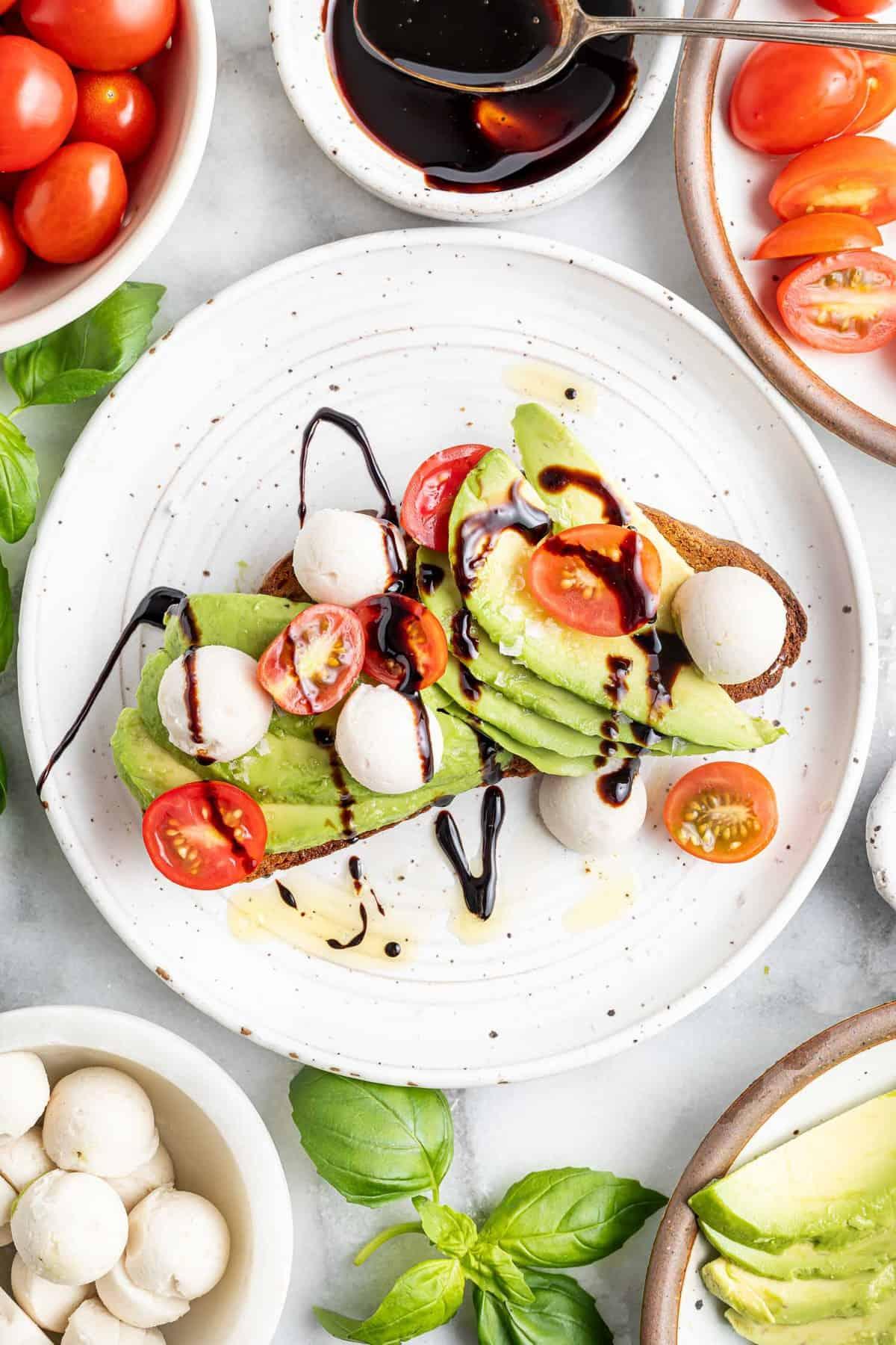 Caprese avocado toast drizzled with balsamic glaze.