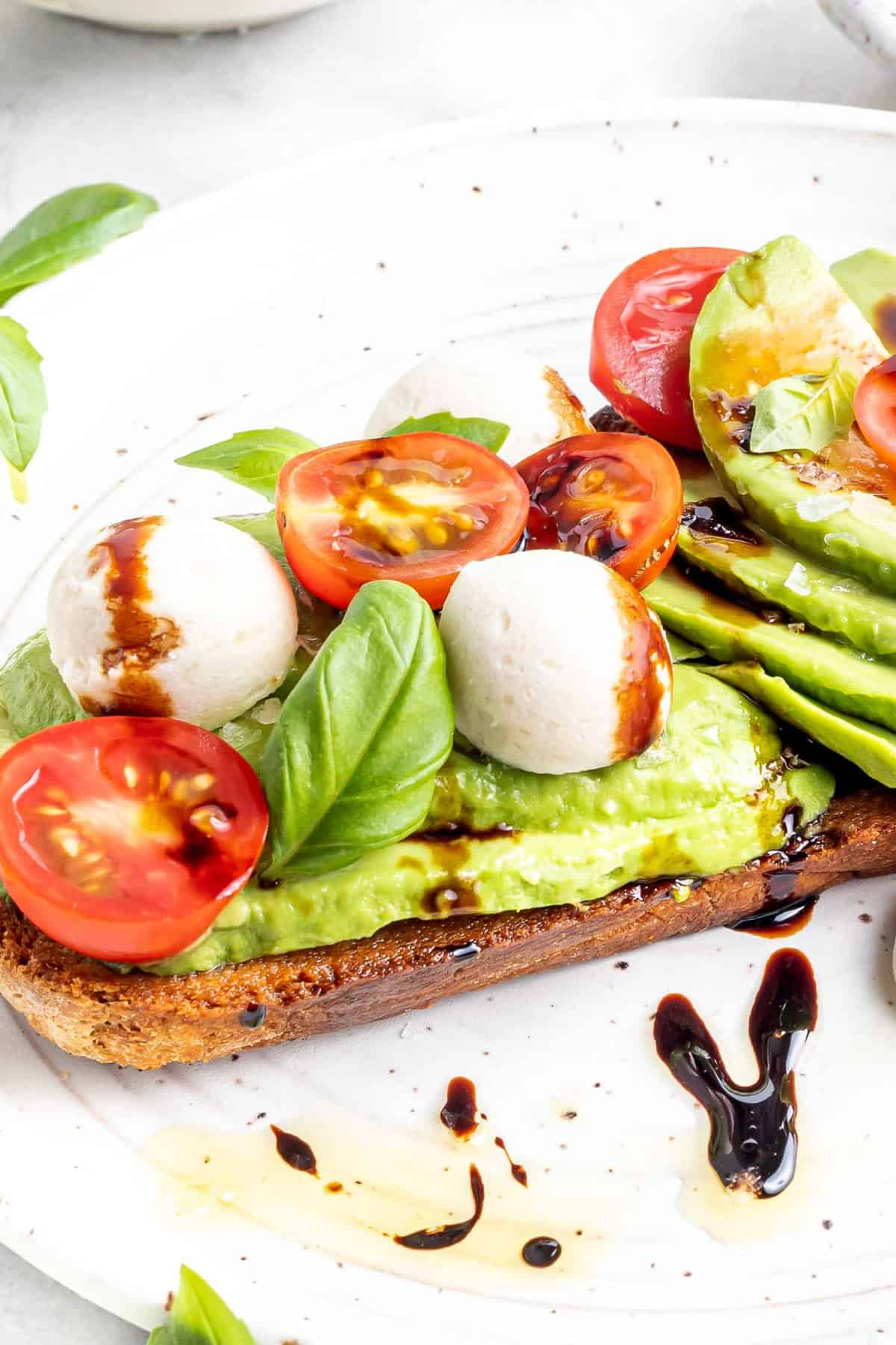 Close up view of avocado toast topped with caprese salad.