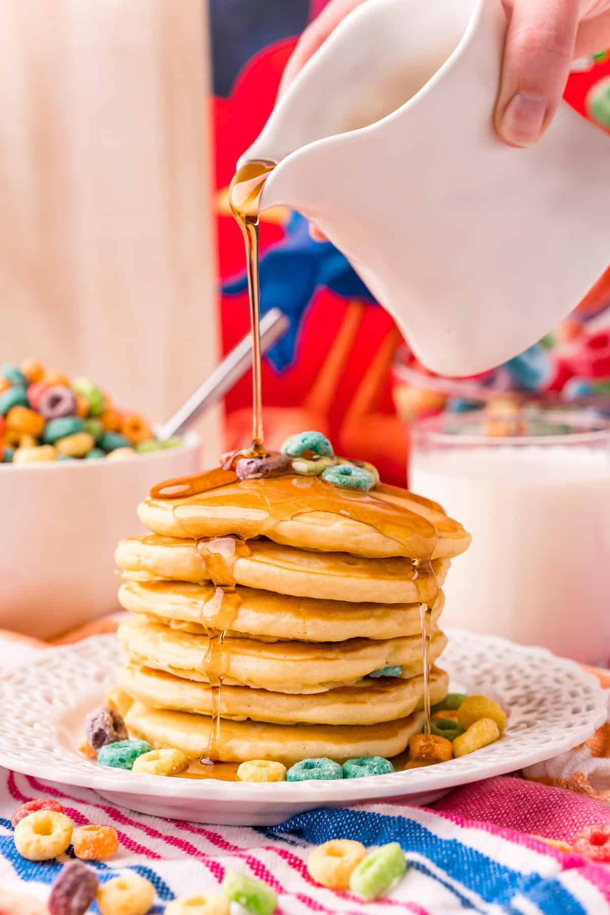 Syrup being poured on a tall stack of froot loop pancakes.