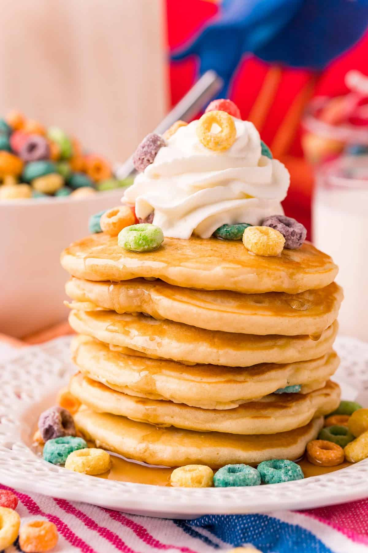 Pancakes topped with Froot Loops cereal, whipped cream, and syrup.