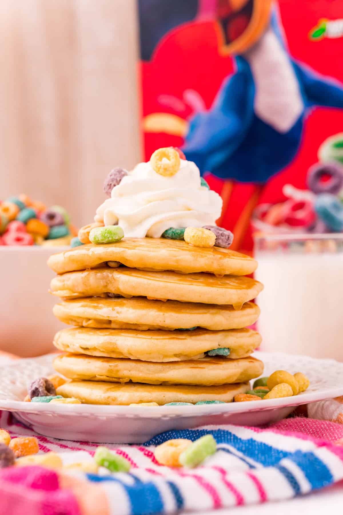 Pancakes topped with whipped cream and cereal.