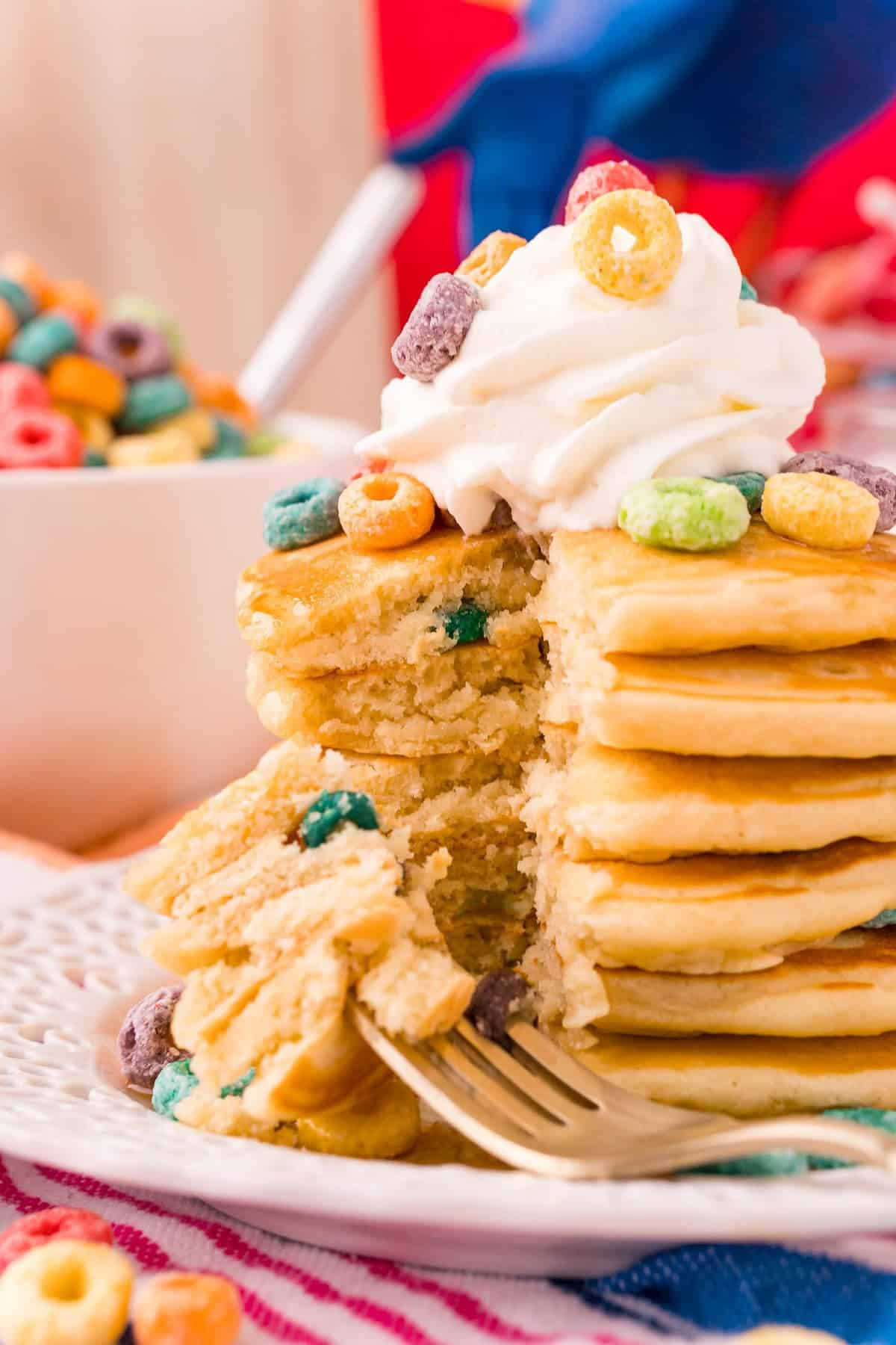 Froot loop pancakes in a large stack, a wedge cut out to show texture.