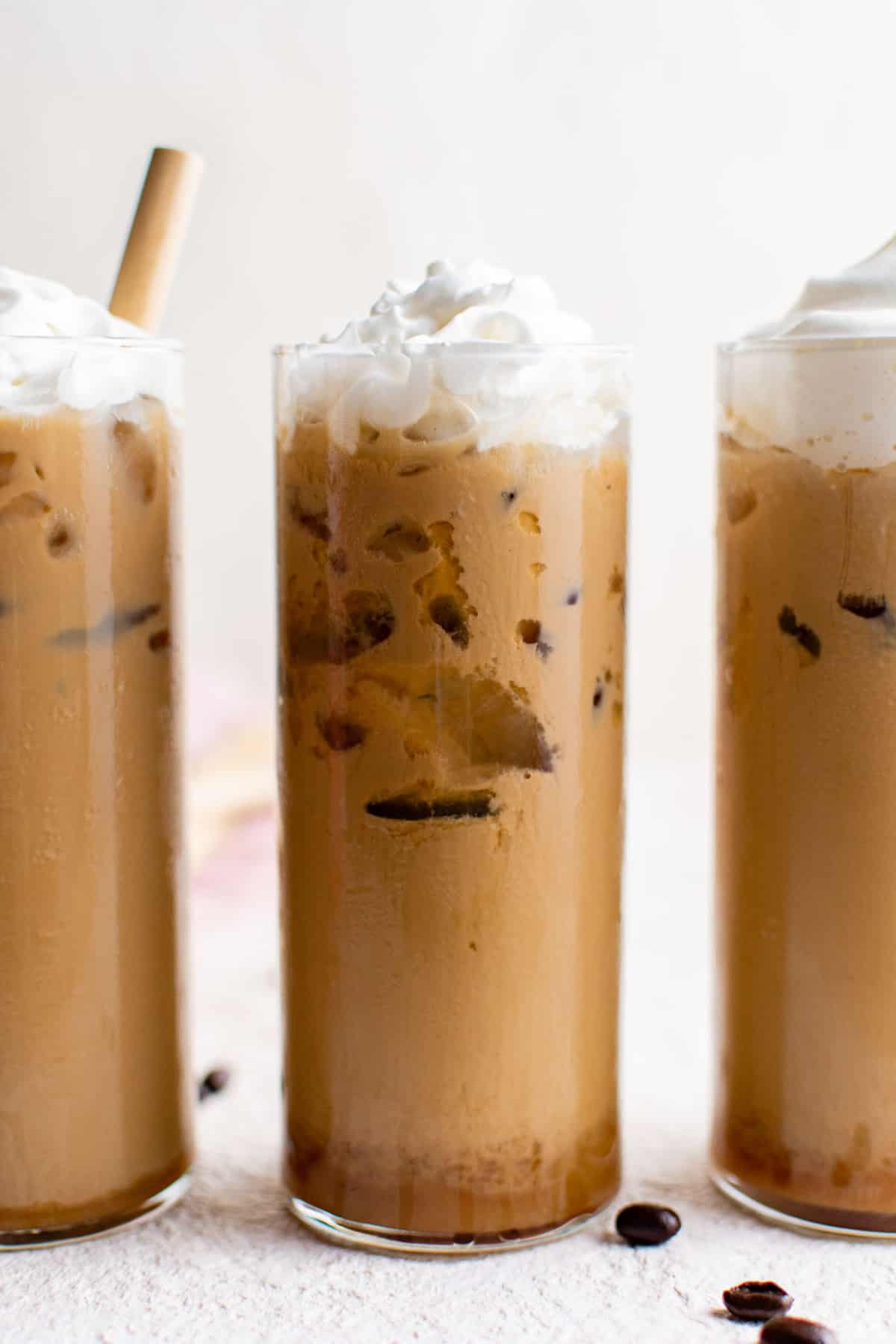 Three glasses of iced coffee topped with whipped cream.