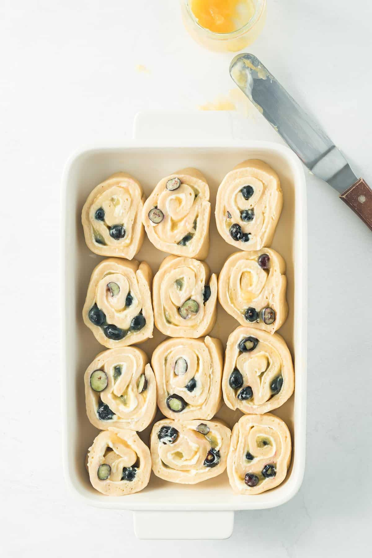 Unbaked blueberry rolls in a white baking dish.