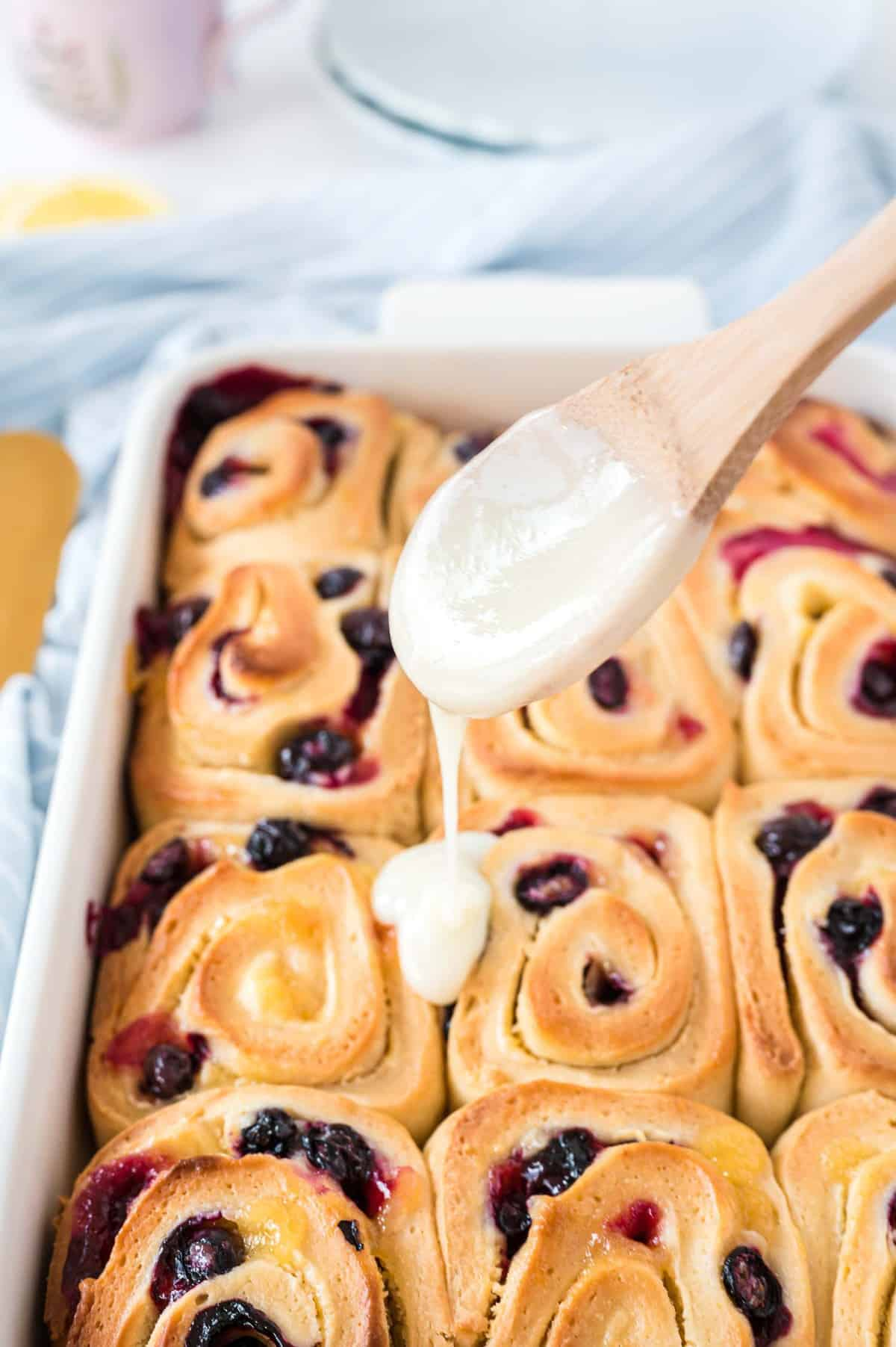 Glaze being drizzled on blueberry lemon rolls.