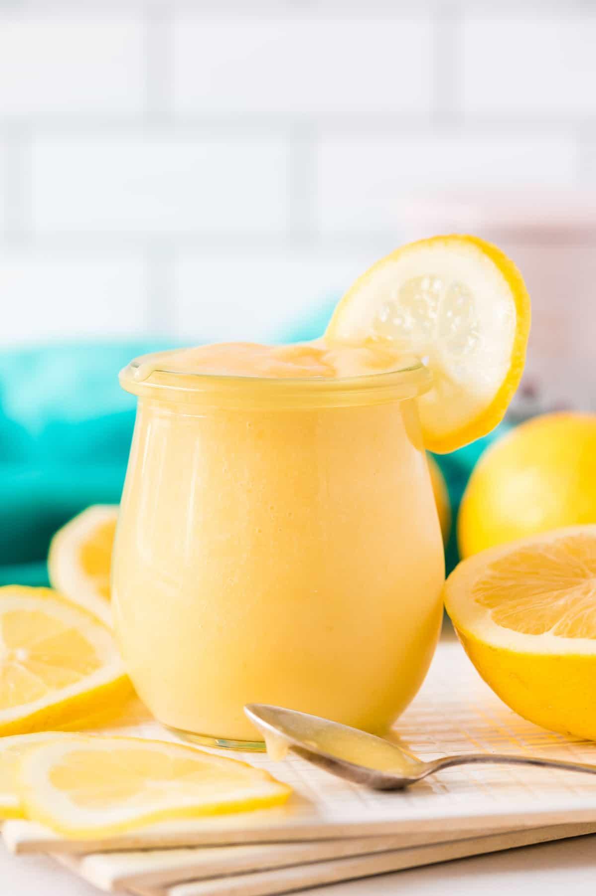 Lemon curd in a jar garnished with a wheel of fresh lemon.