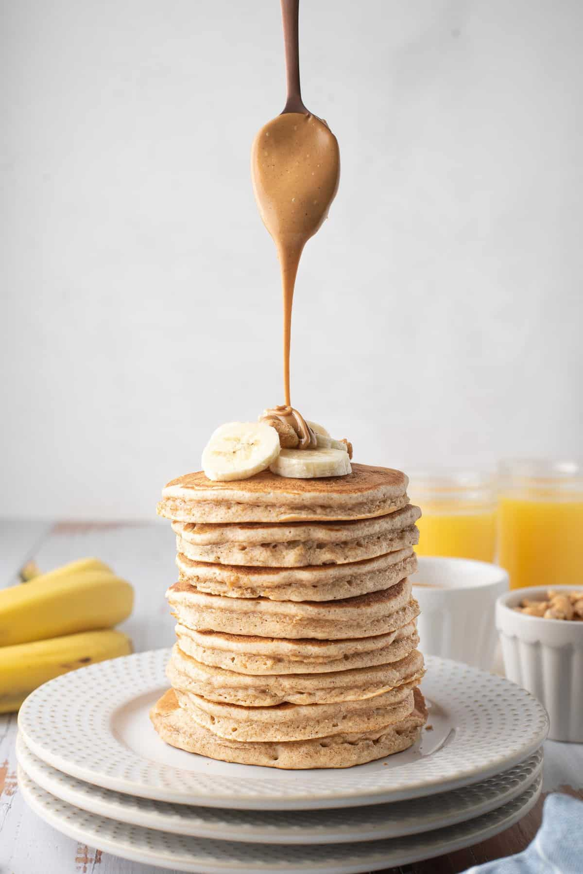 Peanut butter being drizzled from a spoon onto a very tall stack of pancakes.