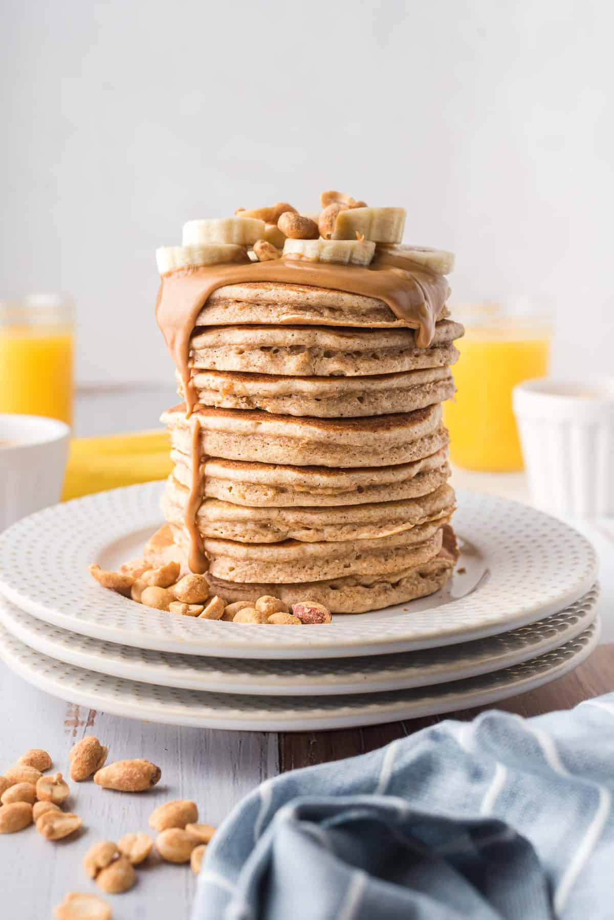 Tall stack of pancakes dripping with peanut butter and topped with banana slices.