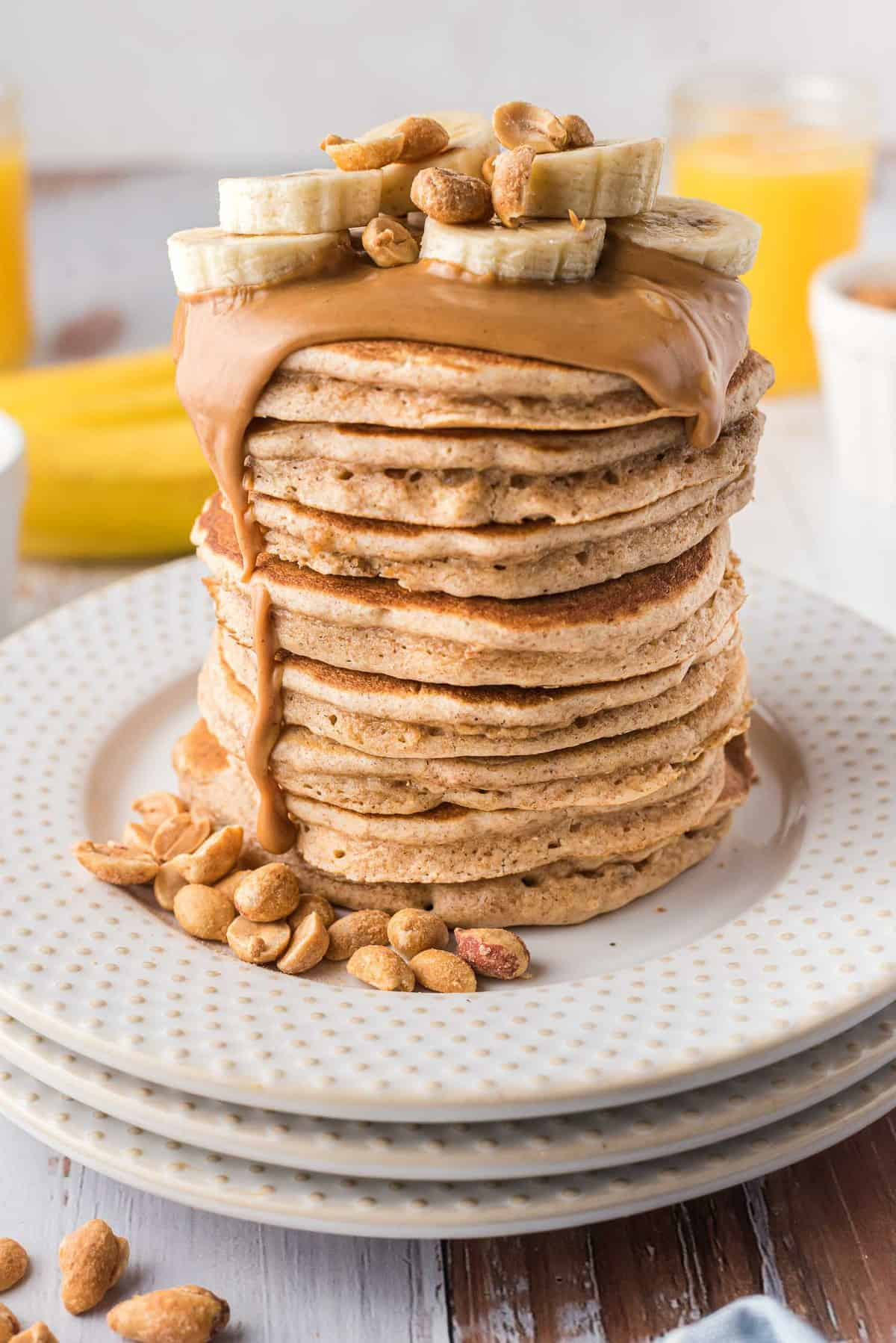 Very tall stack of pancakes topped with melted peanut butter, banana slices, and peanuts.