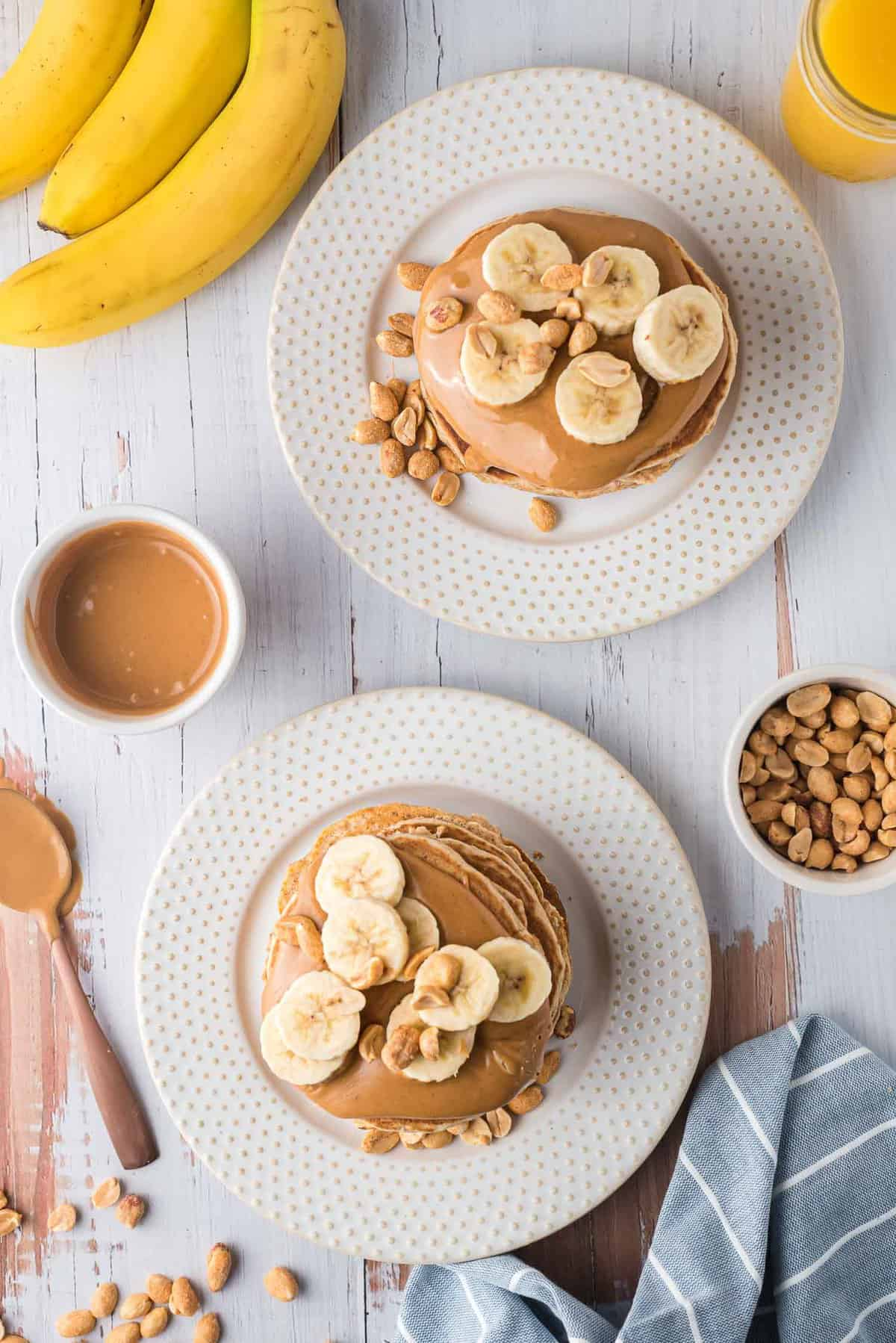 Overhead view of two stack of pancakes on white plates, topped with peanut butter, peanuts, and banana slices.