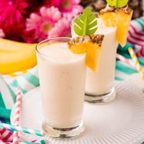 Two tall glasses full of light yellow smoothie, garnished with fresh pineapple.