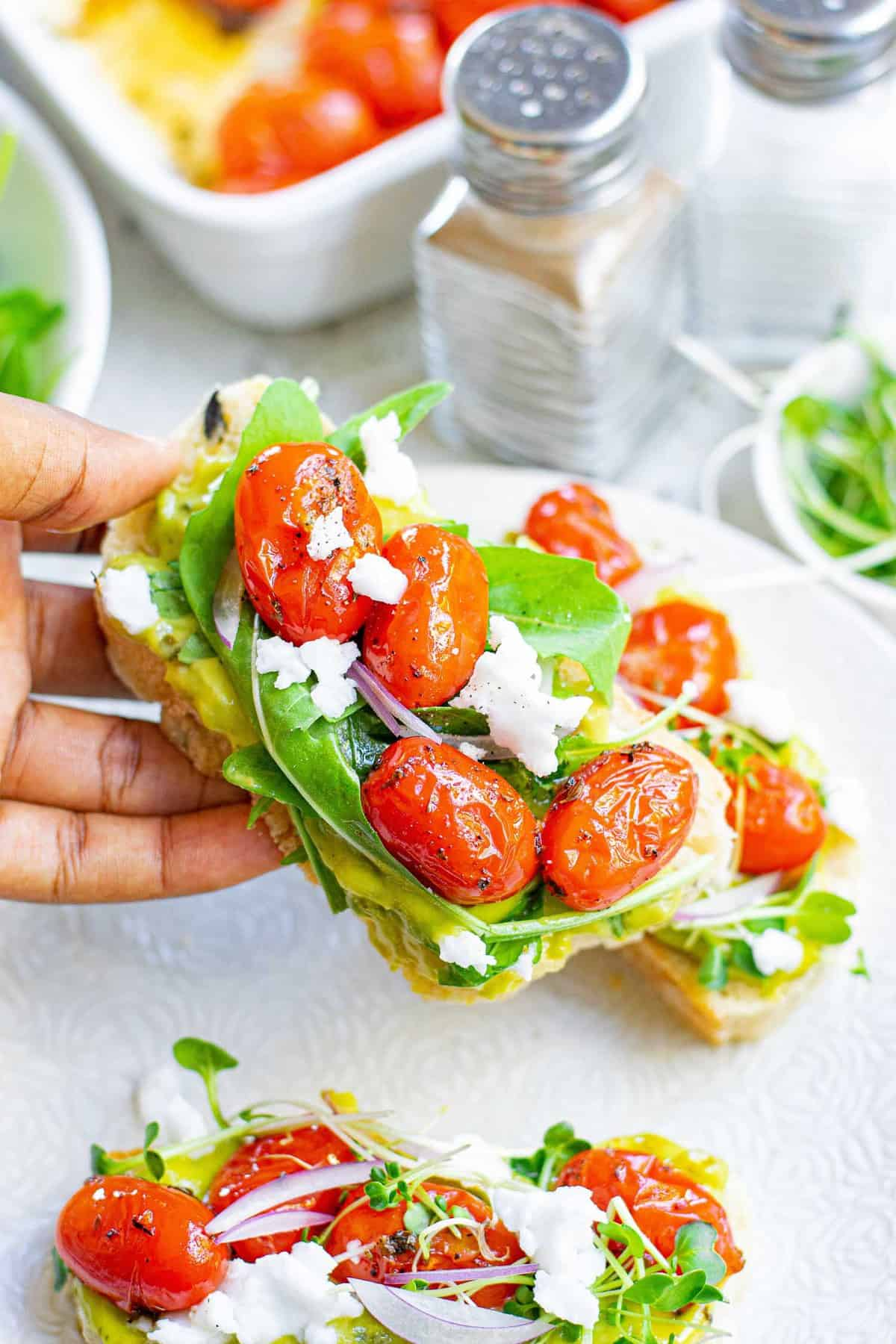 Hand holding a piece of toast topped with avocado, tomato, feta, and greens.
