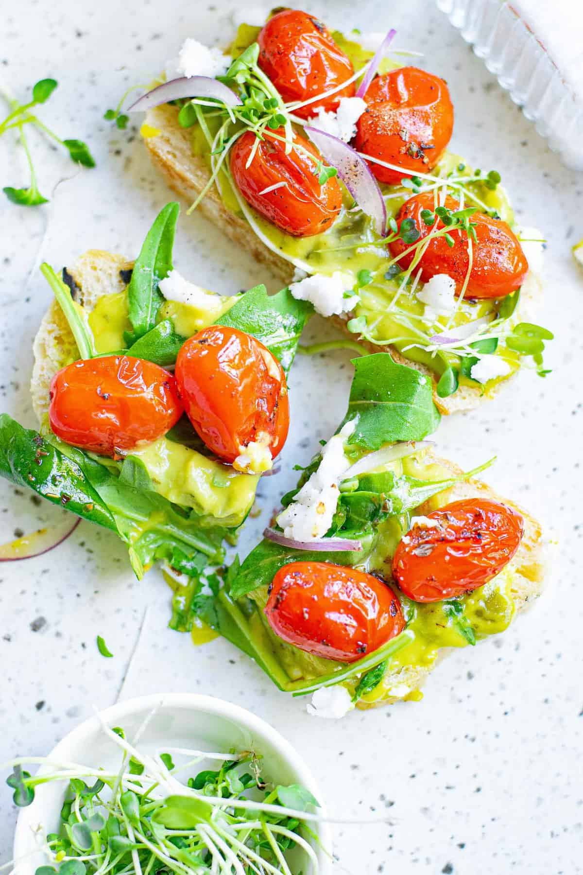 Toast topped with guacamole, tomatoes, feta, and greens.