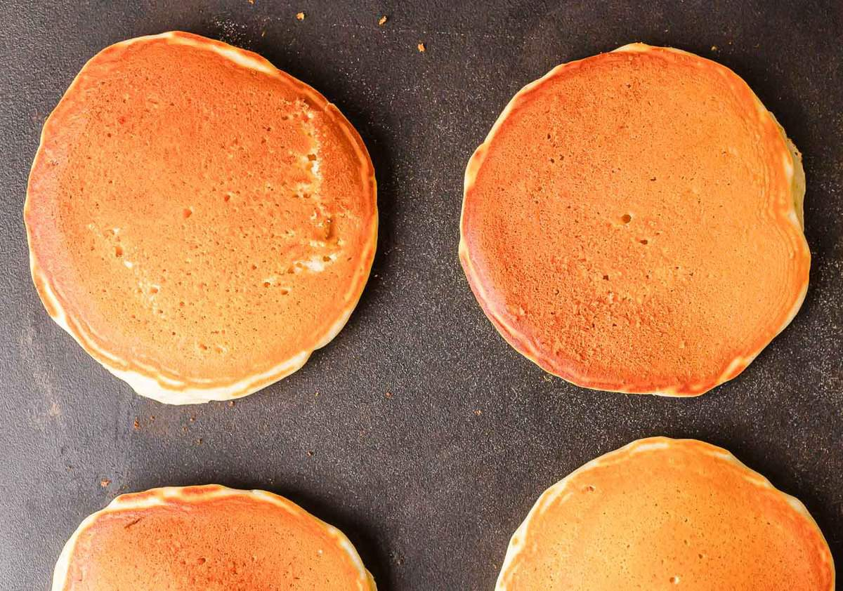 Fully cooked pancakes on a griddle.