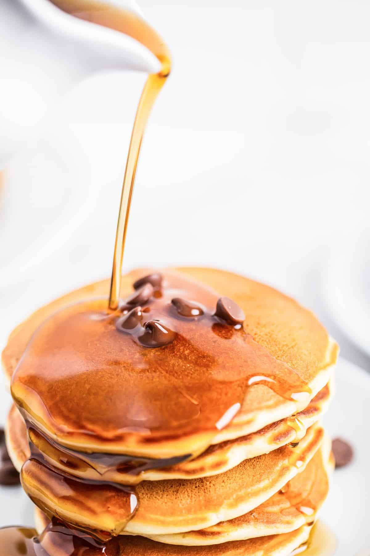 Close up of syrup being poured on pancakes.