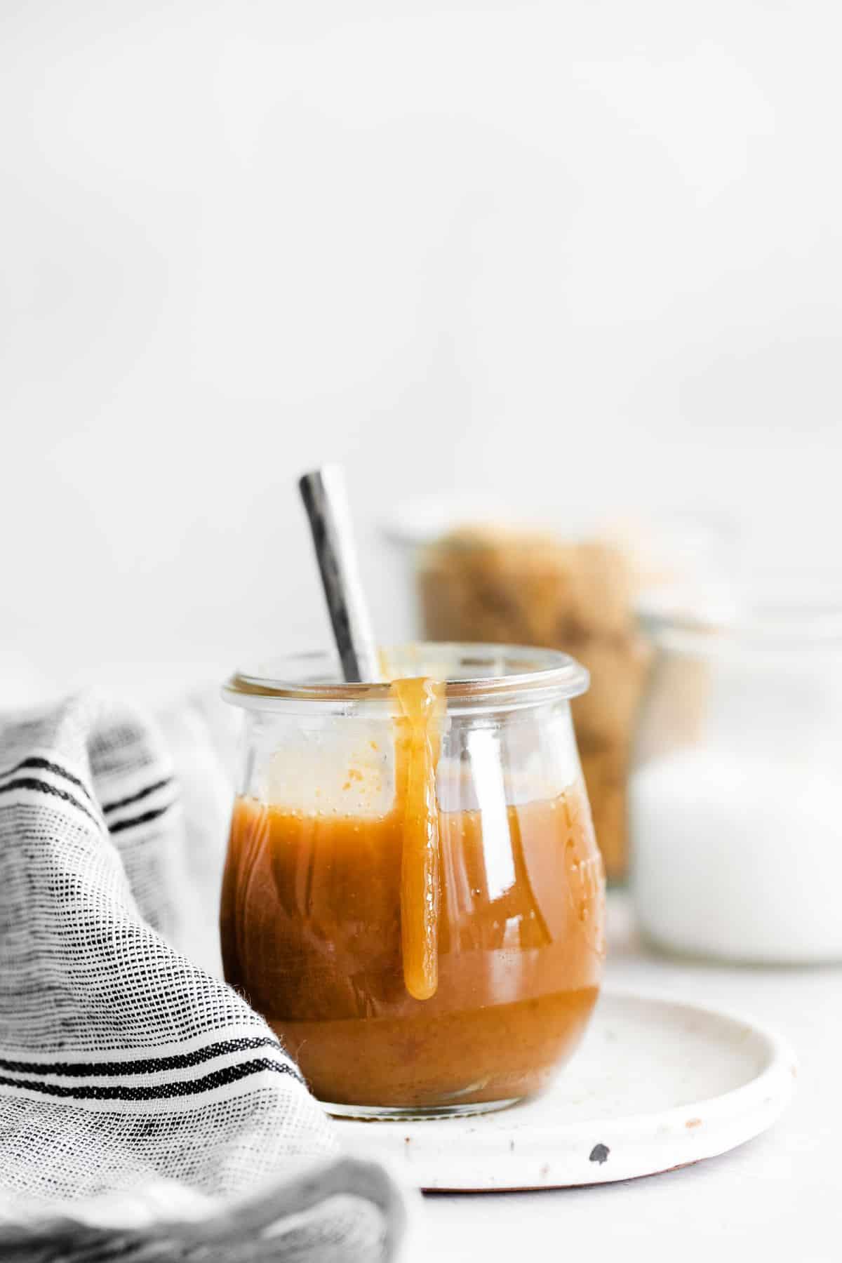 Jar of vegan caramel with sauce dripping down side of jar.