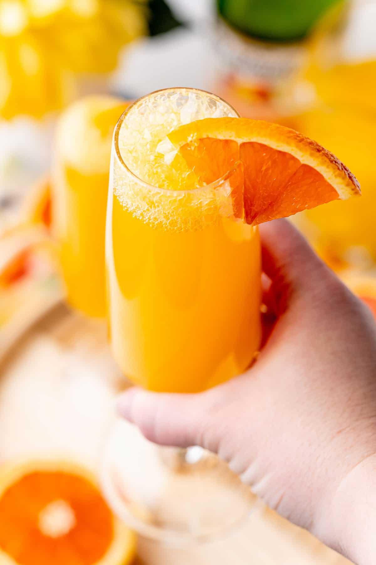 Hand holding a mimosa mocktail garnished with orange slice.