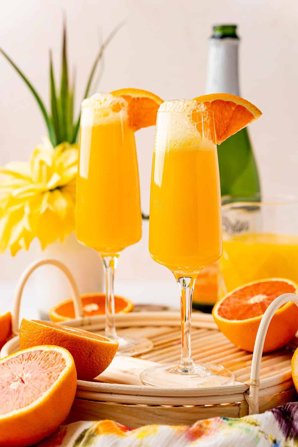 Two orange juice cocktails in champagne flutes.