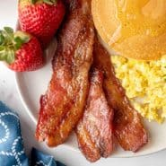 Candied bacon on a plate with pancakes, eggs, strawberries.