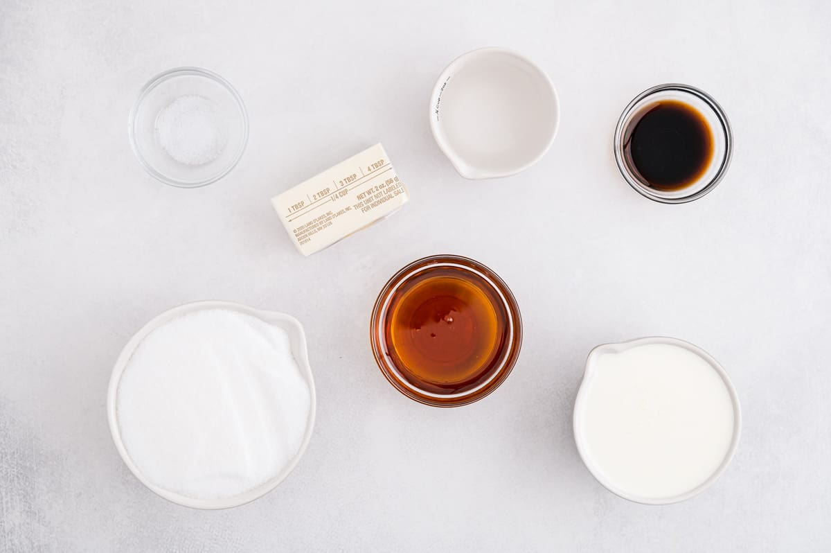 Overhead view of ingredients needed for recipe: cream, vanilla, butter, salt, corn syrup, sugar.