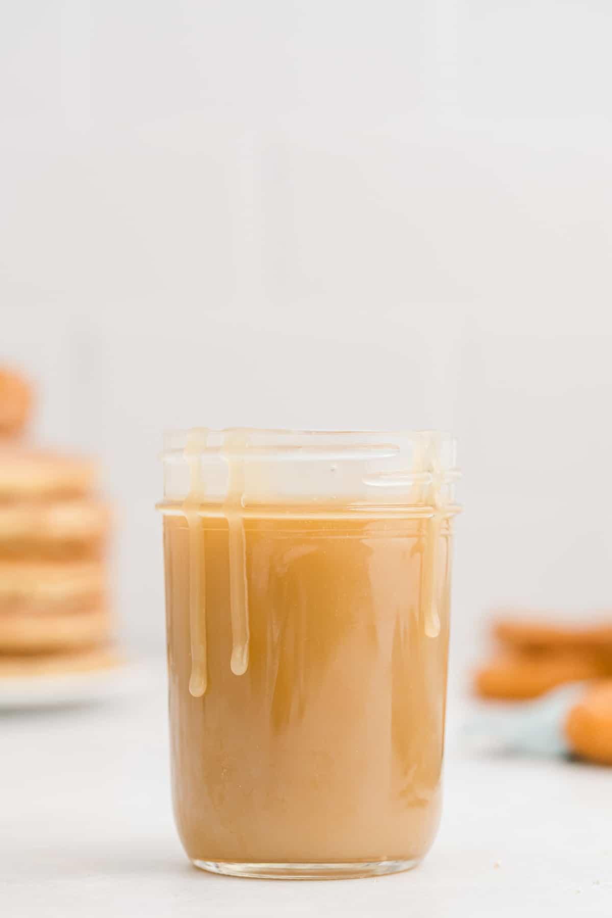 Caramel in a jar and dripping down sides of jar.